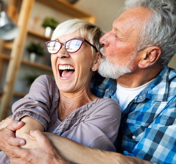 Older couple laughing together after dental implant tooth replacement