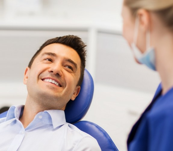 Man smiling at dentist during dental implant consultation
