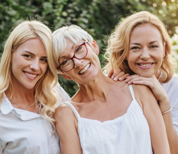 Three generations of woman smiling after dental implant tooth replacement