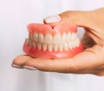 Hands holding dental implant supported full dentures