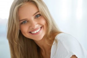 woman blonde hair smiling perfect teeth