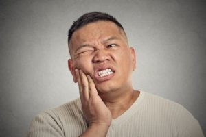 Pained man with hand on cheek has dental emergency