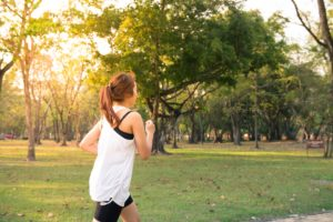 Woman with tooth pain running in park.