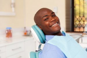 Man smiles after treatment from his Marion oral surgeon